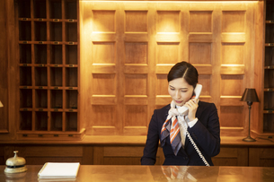 電話対応をするコンシェルジュの女性の写真素材 [FYI04106806]