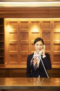 電話対応をするコンシェルジュの女性の写真素材 [FYI04106807]
