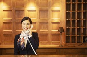電話対応をするコンシェルジュの女性の写真素材 [FYI04106808]