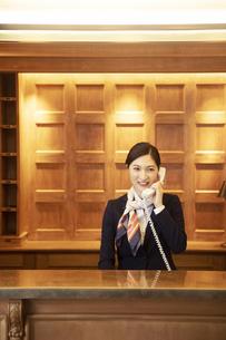 電話対応をするコンシェルジュの女性の写真素材 [FYI04106810]