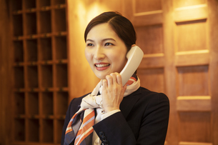 電話対応をするコンシェルジュの女性の写真素材 [FYI04106811]
