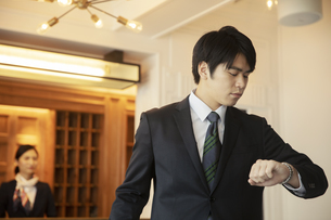 ホテルで腕時計を見る男性の写真素材 [FYI04106813]