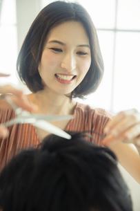 美容室で髪を切る女性の美容師の写真素材 [FYI04106842]