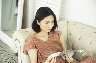 ソファーで雑誌を読む20代女性の写真素材 [FYI04106847]