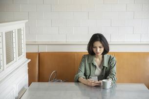 カフェでコーヒーを飲みながらスマートフォンを見る女性の写真素材 [FYI04106849]