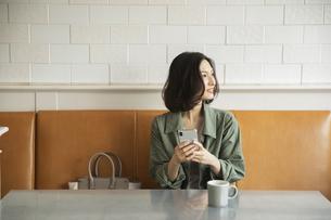 カフェでコーヒーを飲みながらスマートフォンを見る女性の写真素材 [FYI04106852]