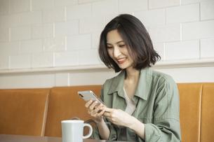 カフェでコーヒーを飲みながらスマートフォンを見る女性の写真素材 [FYI04106853]