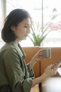 カフェでコーヒーを飲みながらスマートフォンを見る女性の写真素材 [FYI04106857]