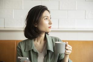 カフェでコーヒーを飲みながらスマートフォンを見る女性の写真素材 [FYI04106858]