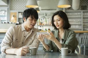 カフェで会話をする若いカップルの写真素材 [FYI04106869]