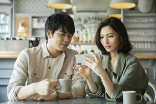 カフェで会話をする若いカップルの写真素材 [FYI04106870]