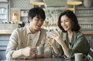 カフェで会話をする若いカップルの写真素材 [FYI04106871]