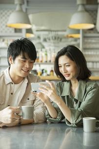 カフェで会話をする若いカップルの写真素材 [FYI04106878]