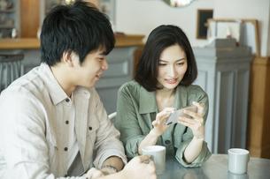 カフェで会話をする若いカップルの写真素材 [FYI04106881]