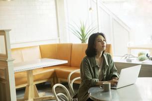 カフェでコーヒーを飲みながらパソコンを見る女性の写真素材 [FYI04106891]