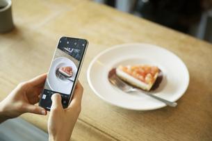 スマートフォンでケーキの写真を撮る女性の手元の写真素材 [FYI04106899]