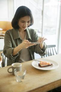 スマートフォンでケーキの写真を撮る女性の写真素材 [FYI04106901]