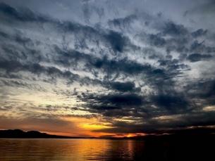 日没と雲と凪いだ海の写真素材 [FYI04106934]