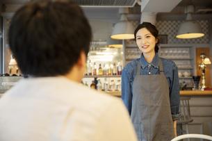 カフェで接客をする女性店員と男性客の写真素材 [FYI04106953]