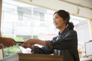 カフェで接客をする女性店員と男性客の写真素材 [FYI04106955]