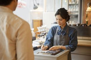 カフェで接客をする女性店員と男性客の写真素材 [FYI04106956]
