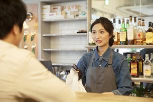カフェで接客をする女性店員と男性客の写真素材 [FYI04106960]