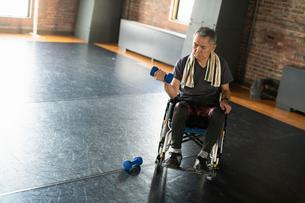 車椅子に乗りダンベルを使うシニアの男性の写真素材 [FYI04107311]