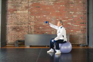 バランスボールで体幹トレーニングするシニアの男性の写真素材 [FYI04107315]