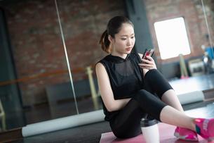 フィットネスアプリをチェックする女性の写真素材 [FYI04107343]