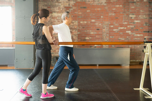 トレーナーと一緒にリハビリで歩行訓練をするシニアの男性の写真素材 [FYI04107384]