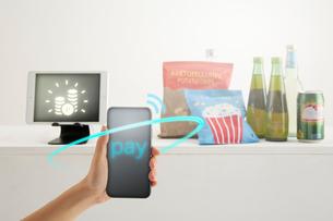 セルフレジに置かれた食品とスマートフォンをかざす女性の手の写真素材 [FYI04108917]