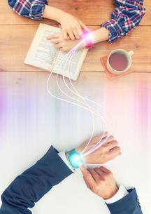 男性と女性のスマートウォッチを繋ぐ光線の写真素材 [FYI04108926]