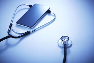 テーブル上でスマホに当てられた聴診器の写真素材 [FYI04108994]