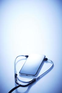 テーブル上でスマホに当てられた聴診器の写真素材 [FYI04108995]