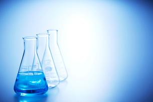一つだけ青い液体の入った3つ並びの三角フラスコの写真素材 [FYI04109003]