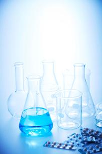 青い液体の入った三角フラスコとその他複数のフラスコとビーカーに錠剤の写真素材 [FYI04109010]