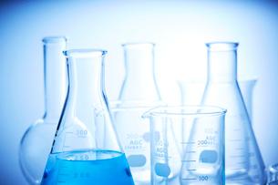 青い液体の入った三角フラスコとその他複数のフラスコとビーカーの写真素材 [FYI04109011]