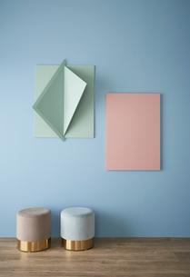 青い壁と立体的なオブジェとピンクのパネルと二つのスツールの写真素材 [FYI04109064]