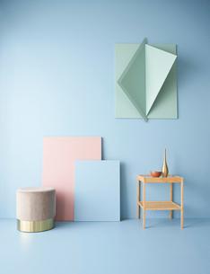 青い壁と立体的なオブジェにピンクと青いパネルと椅子にスツールの写真素材 [FYI04109067]
