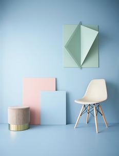 青い壁と立体的なオブジェにピンクのパネルとスツールとサイドテーブルの写真素材 [FYI04109071]