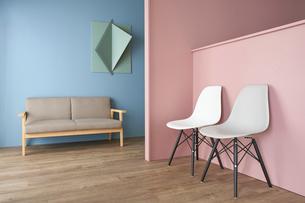 青い壁と立体的なオブジェにピンクの壁の前に置かれた二脚の椅子の写真素材 [FYI04109087]