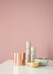 ピンクの壁の前に置かれたテーブルの上のキャンドルスタンドと器たちの写真素材 [FYI04109097]