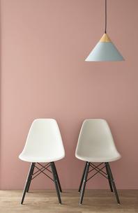 ピンクの壁の前の二脚の椅子とペンダントライトの写真素材 [FYI04109105]