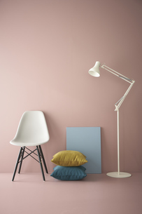 ピンクの壁と床に置かれた椅子とフロアーライトにクッションと青いパネルの写真素材 [FYI04109108]