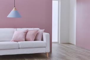 ピンクの壁の前のソファーとペンダントライトに奥行のある空間の写真素材 [FYI04109117]