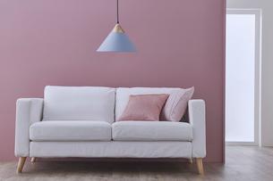 ピンクの壁の前のソファーとペンダントライトに奥行のある空間の写真素材 [FYI04109118]