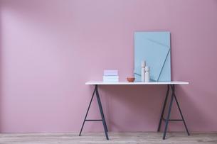 ピンクの壁の前に置かれたデスクとその上の小物の写真素材 [FYI04109123]