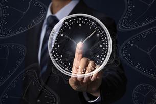 人差し指で時計に触れるサラリーマンの写真素材 [FYI04109563]