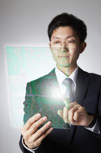 透明のタブレットでプログラミングするサラリーマンの写真素材 [FYI04109569]