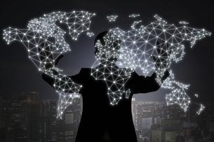 夜の街を背景に両手で世界地図のホログラムを出す人影の写真素材 [FYI04109571]